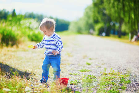 Toddler playing with sand molds, bucket and shovel, making mudpies and gathering small stones. Outdoor creative activities for kids