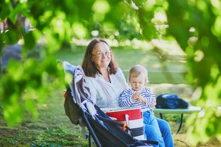 Feliz mujer de mediana edad con niña en un día soleado de verano en el parque. Abuela divirtiéndose con su nieta al aire libre Foto de archivo