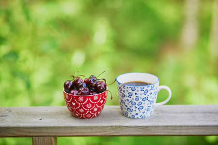 Cup of black coffee and bowl of sweet cherries