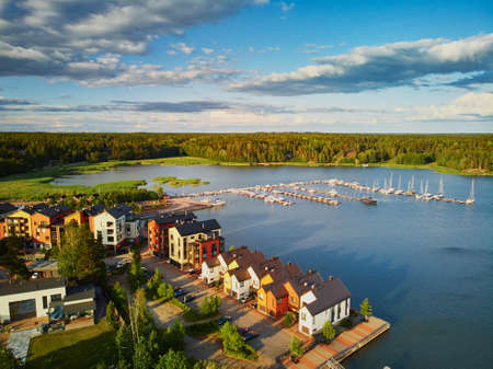 Scenic aerial view of colorful boats near wooden berth and buildings in the countryside of Finland at sunset
