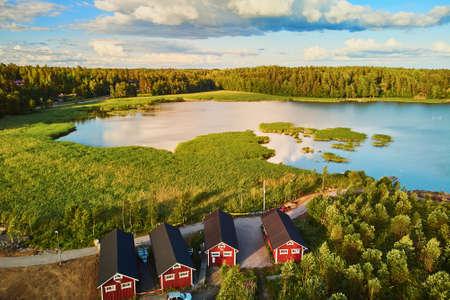 Malerische Luftaufnahme von bunten Booten in der Nähe von Holzliegeplätzen und Gebäuden in der Landschaft Finnlands bei Sonnenuntergang