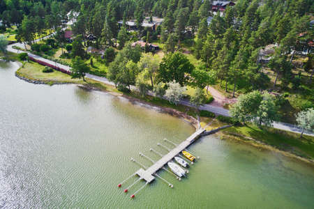Scenic aerial view of colorful boats near wooden berth in the countryside of Finland 版權商用圖片