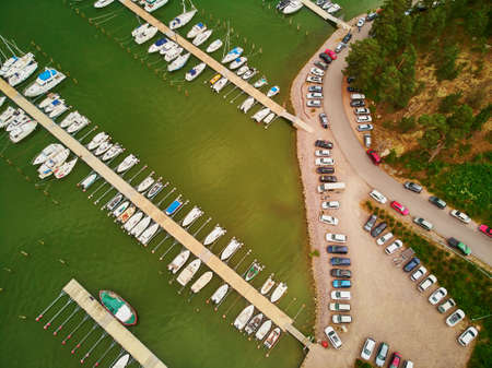 Scenic top down view of colorful boats near wooden berth and large car parking in the countryside of Finland
