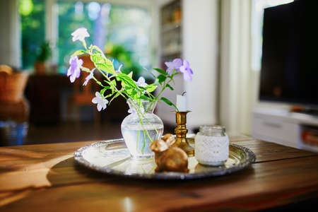 Beautiful home decoration details - flowers in small vase and candle in evening light 版權商用圖片