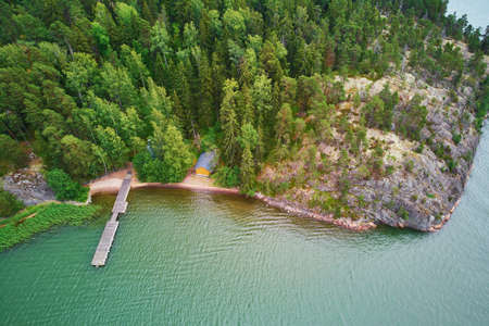 Scenic aerial view of lake house with wooden berth surrounded by pine forest in the countryside of Finland