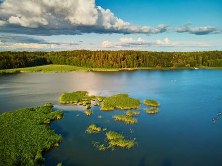 Scenic aerial view of beautiful lake with green grass in the countryside of Finland