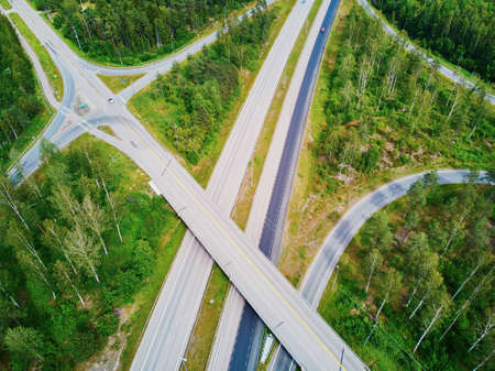 Aerial view of road interchange surrounded by forest in the countryside of Finland, Northern Europe Фото со стока