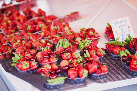 Fresh strawberries, green peas and blueberries for sale on local food market in Helsinki, Finland. Label reads: mix of berries (translation from Finnish) Stock Photo