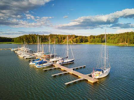 Scenic aerial view of colorful boats near wooden berth in the countryside of Finland Фото со стока