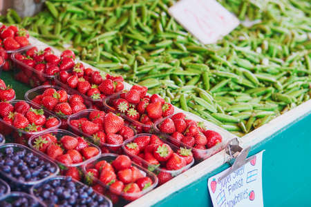Fresh strawberries, green peas and blueberries for sale on local food market in Helsinki, Finland