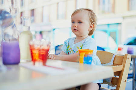 Adorable toddler girl sitting in high chair in cafe or restaurant. Going out with kids concept