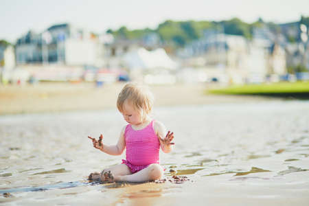 Adorable toddler girl playing with sand on the beach. Outdoor activities for kids