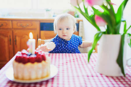 Happy baby girl in blue dress celebrating her first birthday. Little kid with birthday cake and candle