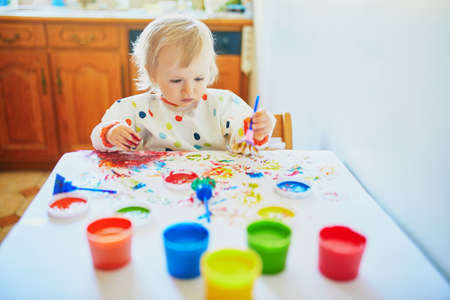 Adorable little girl painting with fingers at home, in kindergaten or preschool. Indoor creative games for kids 写真素材