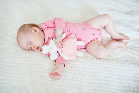 Baby girl having a nap with her favorite mouse toy. Little child sleeping on bed with comforter. Sleep training concept. Infant kid in sunny nursery