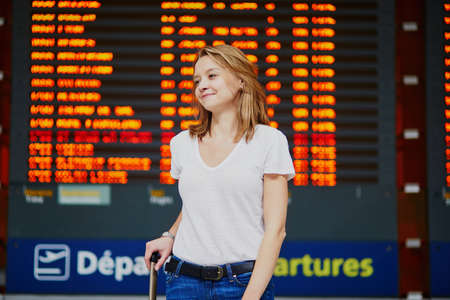 Young woman in international airport with luggage near flight information display Stock Photo