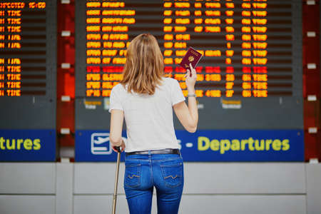 Young woman in international airport with luggage and passport near flight information display Stock Photo - 128659022