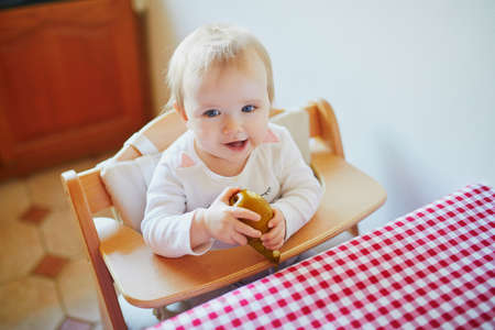 Cute baby girl eating pear in the kitchen. Little kid tasting solids at home. Baby led weaning concept