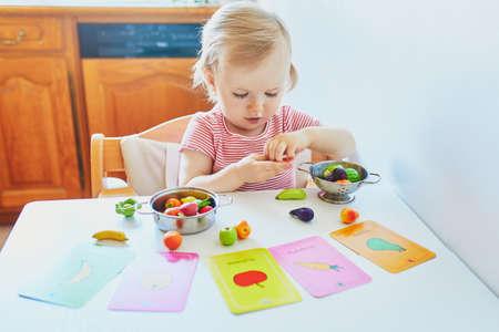 Adorable petite fille jouant avec des fruits et légumes jouets à la maison, à la maternelle ou à l'école maternelle ; essayer de faire correspondre la figurine avec l'image sur une carte. Mots sur des cartes écrites en français. Jeux créatifs d'intérieur pour les enfants Banque d'images