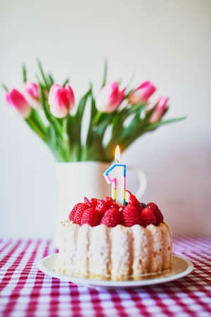 Delicious fruit cake with raspberries and candle in form of number one with bunch of beautiful pink tulipes in vase. Baby's very first birthday concept Stockfoto