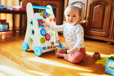 Baby girl sitting on the floor in nursery and playing with wooden push toy. Adorable toddler with baby-walker Banque d'images