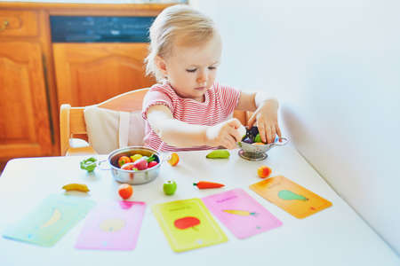 Adorable little girl playing with toy fruits and vegetables at home, in kindergaten or preschool; trying to match figurine with image on a card. Words on cards written in French. Indoor creative games for kids Reklamní fotografie