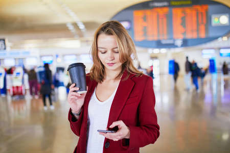 Young woman in international airport with luggage and coffee to go waiting for her flight Stock Photo - 128659376