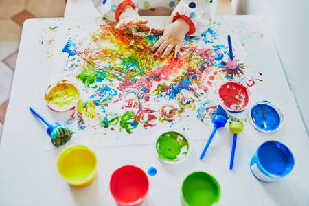 Hand of little girls painting with fingers at home, in kindergaten or preschool. Indoor creative games for kids