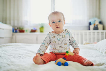 Baby girl sitting on bed. Happy healthy little child at home. Infant kid in sunny nursery Reklamní fotografie