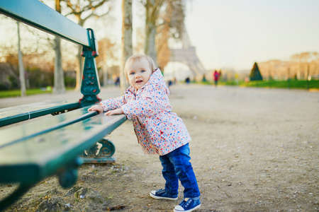 One year old girl standing next to bench near the Eiffel tower. Toddler learning how to walk. Adorable child walking in Paris, France. Traveling with kids