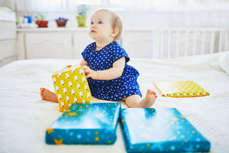 Happy baby girl in blue dress celebrating her first birthday and unpacking her presents
