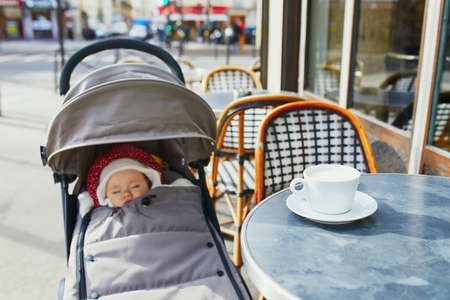 Baby girl sleeping in pram on outdoor terrace of Parisian street cafe with cup of hot coffee on the table. Going out with kids Reklamní fotografie