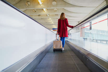 Young woman in international airport with luggage on travelator Stock Photo