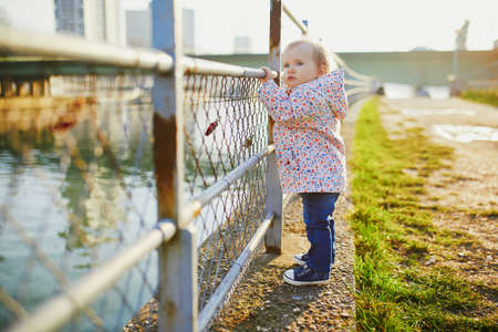 One year old girl standing next to metal fence in park. Toddler learning how to walk. Adorable kid walking in Paris, France