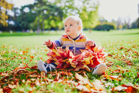 Adorable little girl sitting in large heap of colorful autumn leaves on a fall day in park Reklamní fotografie