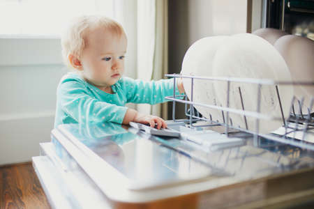 Little child helping to unload dishwasher. Baby girl sitting on the floor in the kitchen. Little child at home Reklamní fotografie