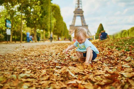 Adorable toddler girl walking on fallen autumn leaves near the Eiffel tower in Paris, France Reklamní fotografie