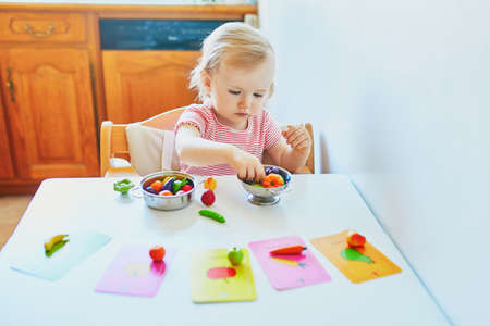 Adorable little girl playing with toy fruits and vegetables at home, in kindergaten or preschool; trying to match figurine with image on a card. Indoor creative games for kids Reklamní fotografie