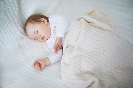 Adorable baby girl sleeping in crib under knitted blanket. Small kid having day nap in parents bed Stock Photo