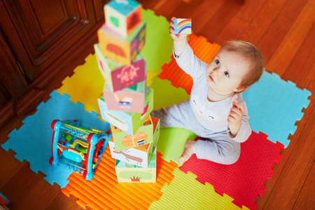 Adorable little girl building a tower at home, in kindergaten or preschool. Indoor creative games for kids