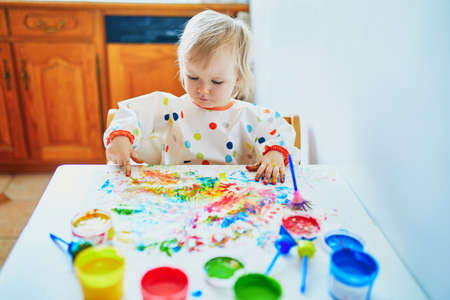 Adorable little girl painting with fingers at home, in kindergaten or preschool. Indoor creative games for kids Archivio Fotografico