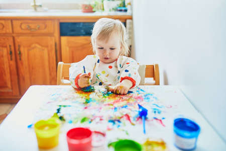 Adorable little girl painting with fingers at home, in kindergaten or preschool. Indoor creative games for kids Reklamní fotografie