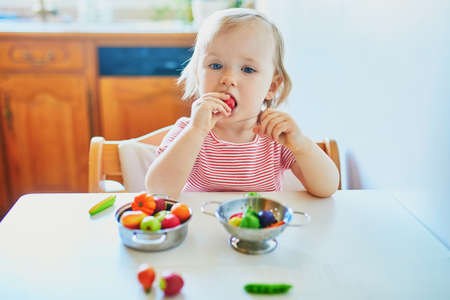 Adorable little girl playing with toy fruits and vegetables at home, in kindergaten or preschool. Indoor creative games for kids Reklamní fotografie