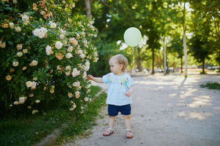 Adorable little girl with green balloon outdoors in park on a sunny day. Toddler looking at flowers. Kid exploring nature Reklamní fotografie