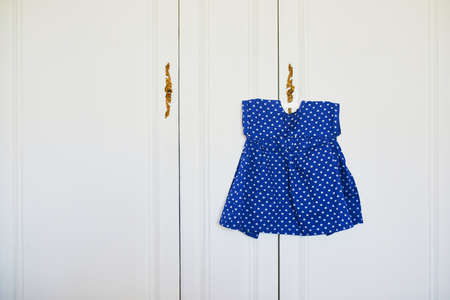 Beautiful blue toddler girl dress on hanger, prepared for event or party. Children fashion concept