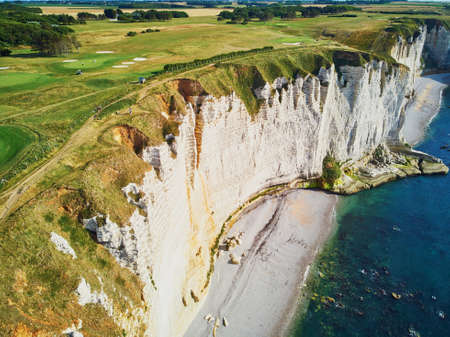 Picturesque panoramic landscape of white chalk cliffs, natural arches and golf fields of Etretat, Seine-Maritime department of Normandy in France.
