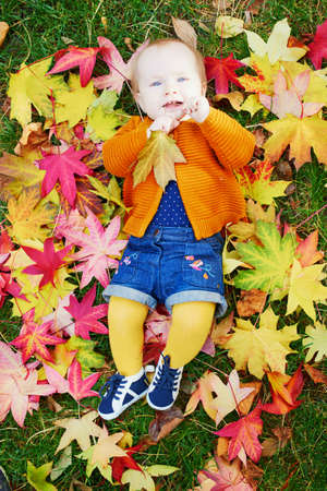 Adorable little girl in bright stylish clothes lying on the grass and playing with colorful autumn leaves on a fall day in park