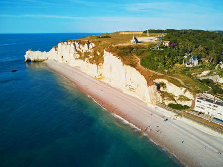Picturesque panoramic landscape of white chalk cliffs and natural arches with view to the village of Etretat, Seine-Maritime department of Normandy in France.