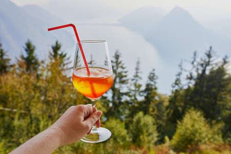 Woman holding glass with cocktail aperol spritz with scenic view to the lake Lugano from Monte Bre in Lugano, canton of Ticino, Switzerland