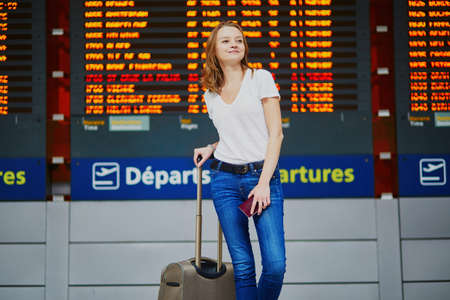 Young woman in international airport with luggage and passport near flight information display Stock Photo